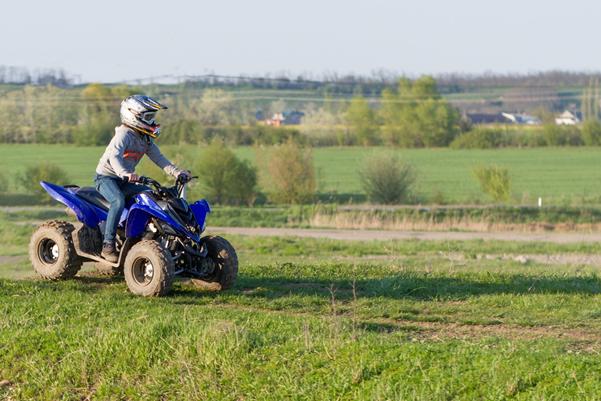 Child riding a quad bike on a grass field
