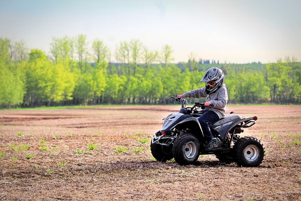 Kid riding a quad bike on an opening mud field