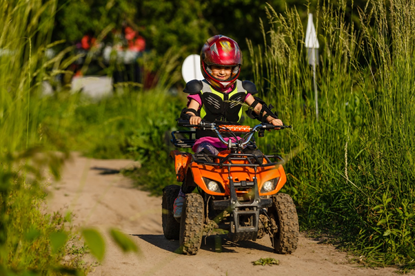 girl riding a kids quads bike on off road dirt track
