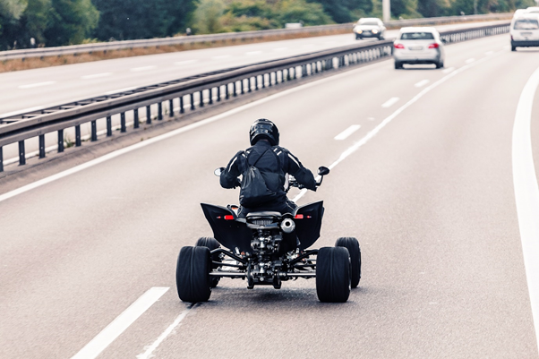 Person riding a quad bike on a dual carriageway